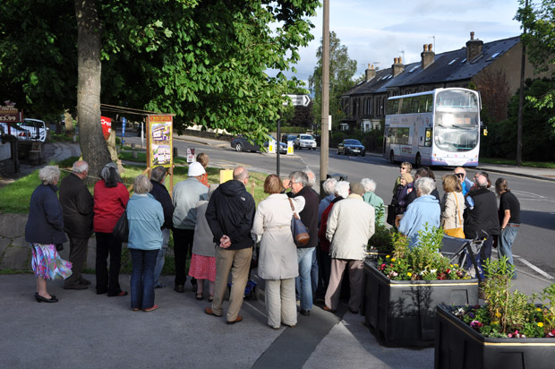 Residents watch a 51 bus pass the bus-themed well dressing outside Crosspool Tavern