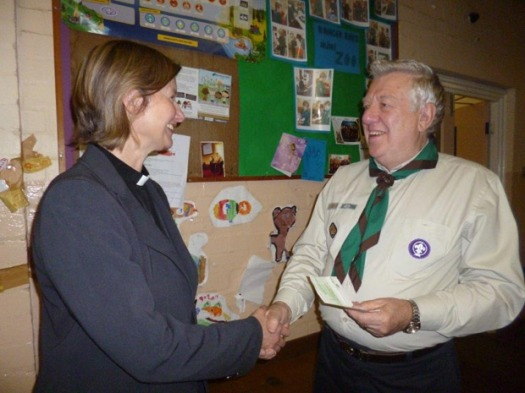 Rev. Frances Eccleston presents the money to group scout leader Michael Holmes