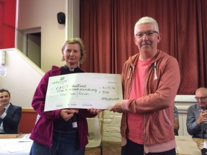 Robin from PACT receives the cheque from festival chair Frances Eccleston