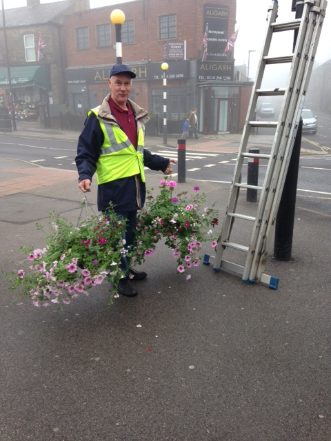 Putting hanging baskets up in the precinct